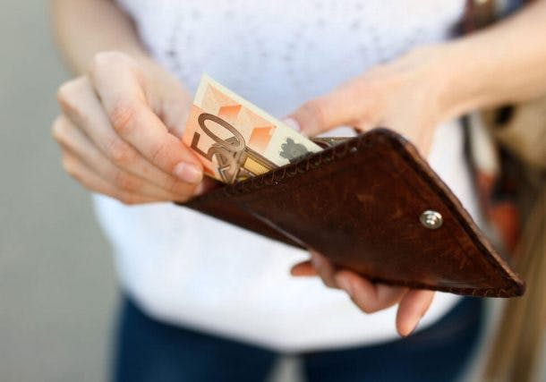 Foto von Frau, die einen Fünzig-Euro-Schein aus ihrem Portemonnaie holt