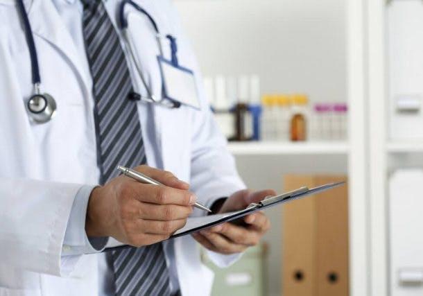 Arzt schreibt etwas auf einem Clipboard mit Kugelschreiber
