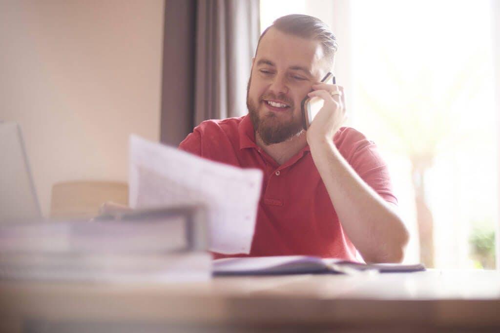 Junger Mann telefoniert und hält Dokument