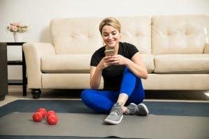 Frau mit Smartphone während des Trainings zuhause
