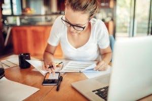 Frau arbeitet zuhause mit Smartphone und Laptopt
